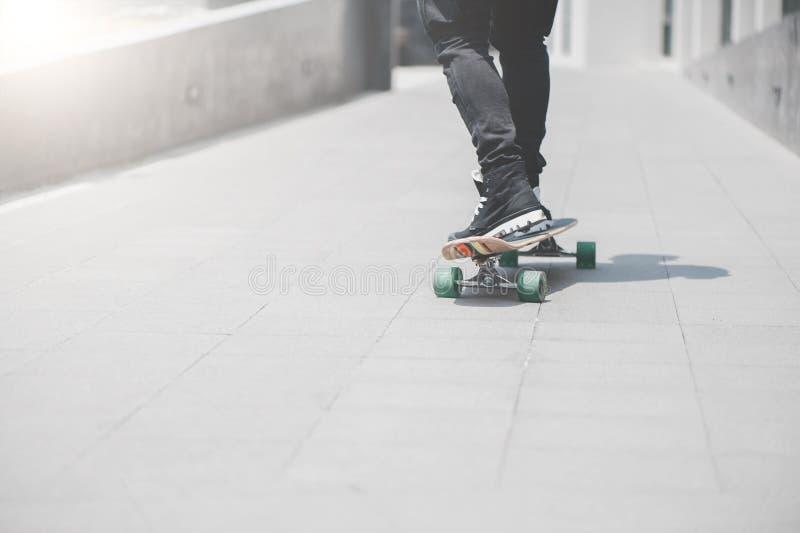 Ciérrese para arriba del skater& x27; piernas de s en el montar a caballo del longboard en la calle adentro al aire libre imágenes de archivo libres de regalías