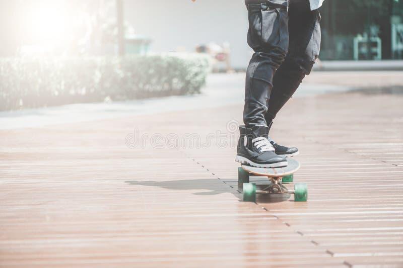 Ciérrese para arriba del skater& x27; piernas de s en el montar a caballo del longboard en la calle adentro al aire libre foto de archivo