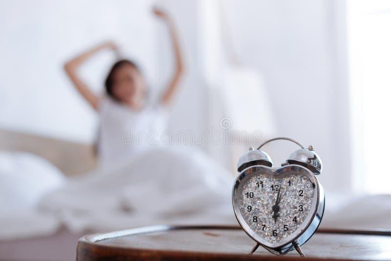 Ciérrese para arriba del sonido y de la mujer del despertador que estiran detrás imagen de archivo