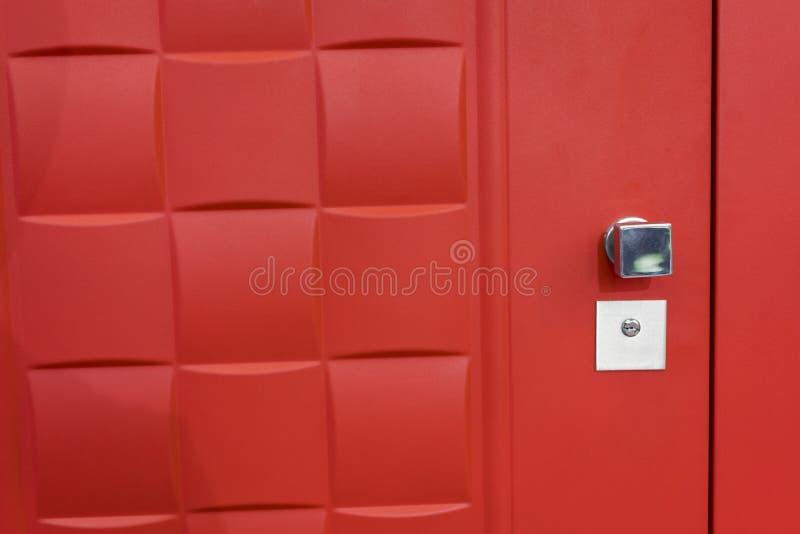 Ciérrese para arriba del tirador de puerta clásico en puerta roja imagen de archivo