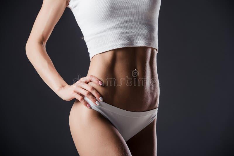 Ciérrese para arriba del torso de la mujer del ajuste con sus manos en caderas La hembra con el abdomen perfecto muscles en fondo imagenes de archivo
