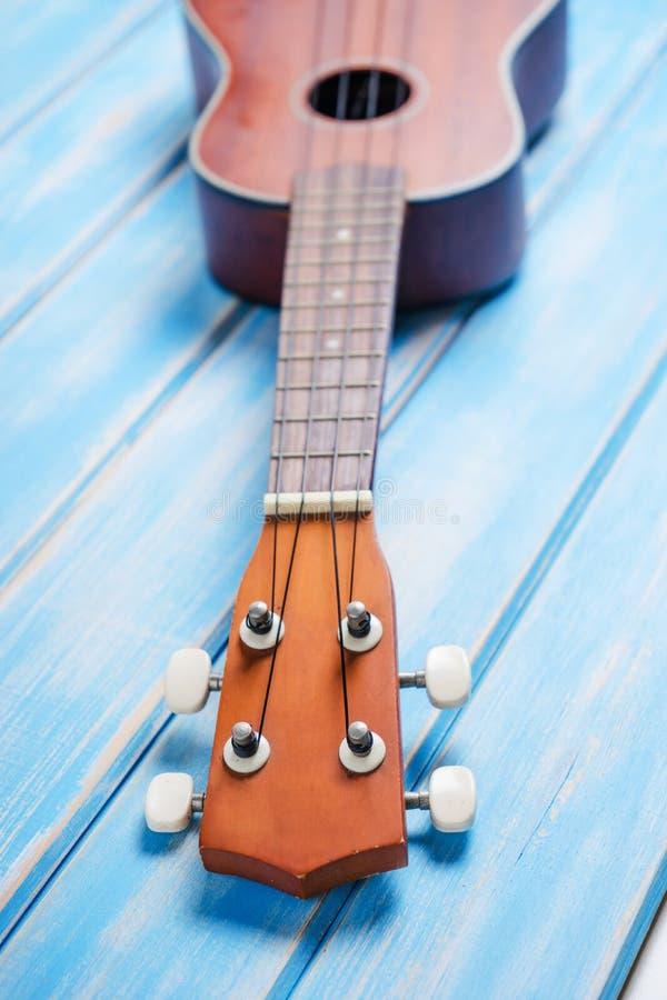 Ciérrese para arriba del ukelele en de madera azul fotografía de archivo