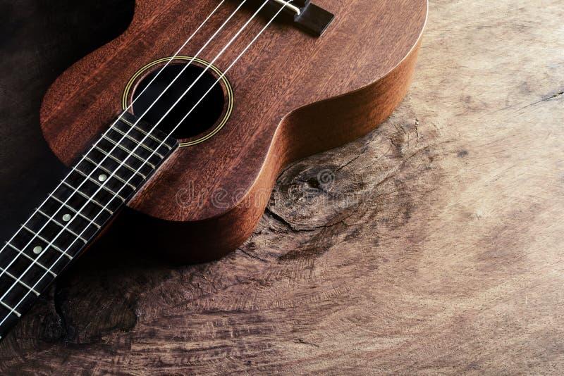 Ciérrese para arriba del ukelele en viejo fondo de madera con la luz suave fotografía de archivo