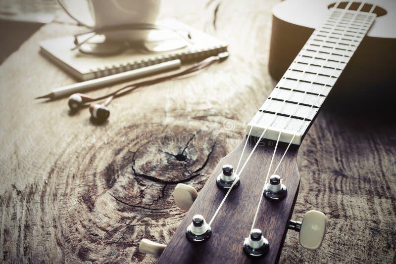 Ciérrese para arriba del ukelele en viejo fondo de madera con la luz suave imagenes de archivo