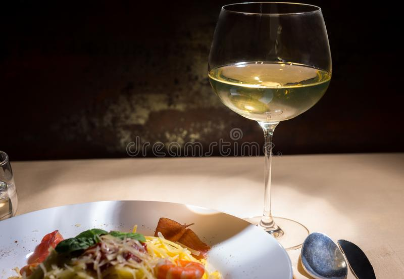 Ciérrese para arriba del vidrio con el vino cerca de las pastas de los espaguetis en la placa blanca imagenes de archivo