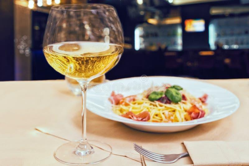 Ciérrese para arriba del vidrio con el vino cerca de las pastas sabrosas de los espaguetis en un resto imagen de archivo