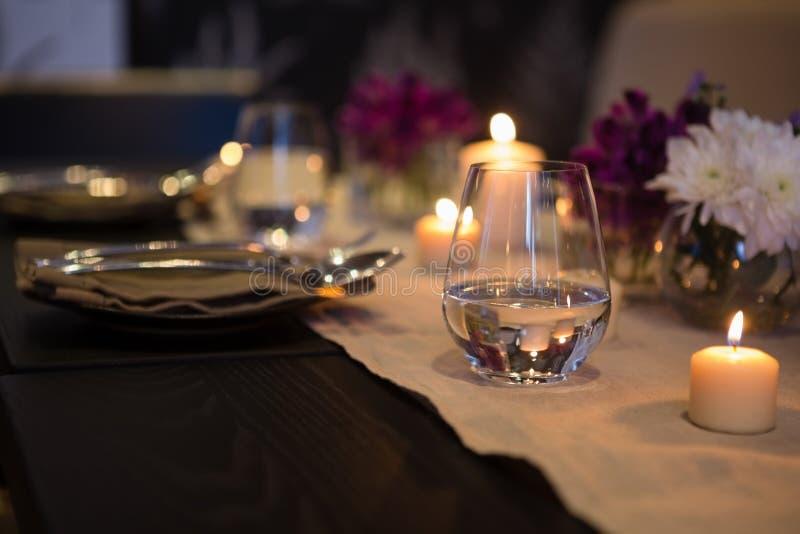 Ciérrese para arriba del vidrio de consumición por las velas encendidas en la mesa de comedor fotografía de archivo
