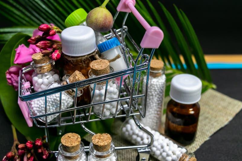 Ciérrese para arriba del vidrio homeopático y de la medicina plástica en flor vieja de madera del boxpink, brote de flor, fruta s fotos de archivo libres de regalías