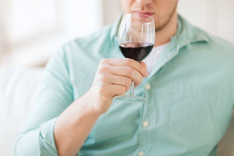 Ciérrese para arriba del vino de consumición del hombre en casa fotografía de archivo