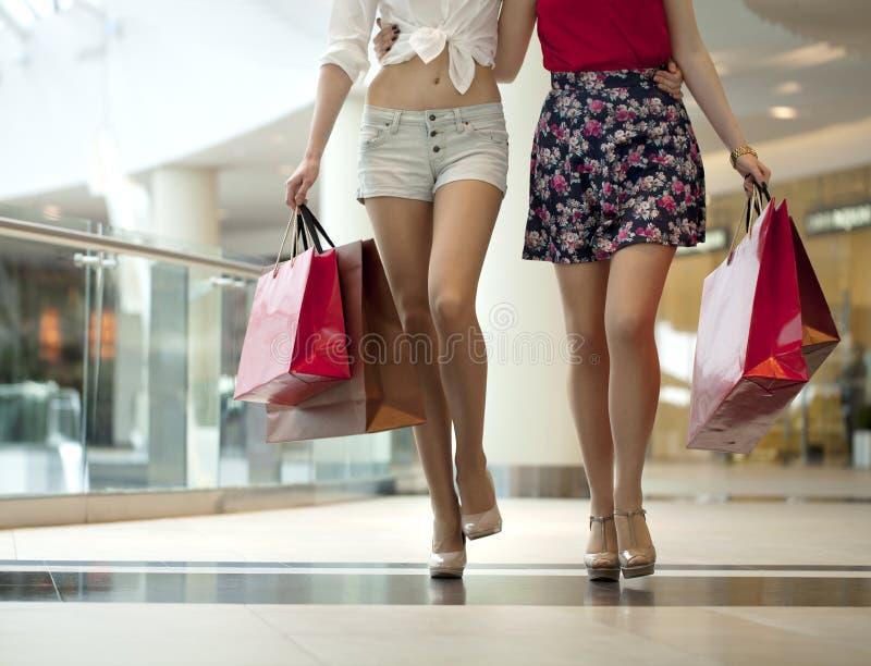 Ciérrese para arriba, dos pares de piernas femeninas con los panieres en su h fotografía de archivo libre de regalías
