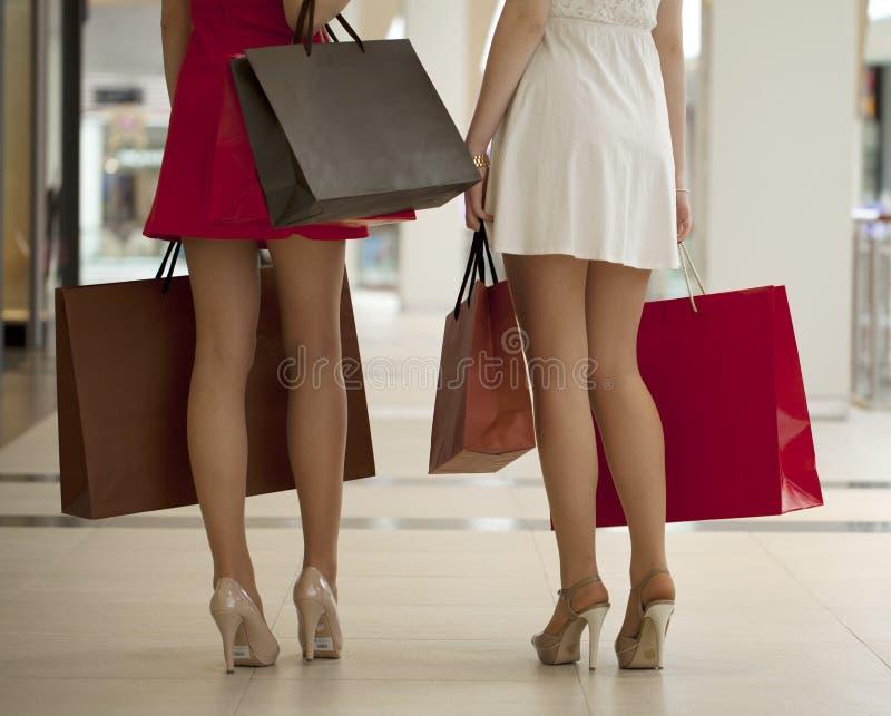 Ciérrese para arriba, dos pares de piernas femeninas con los panieres en su h fotos de archivo libres de regalías