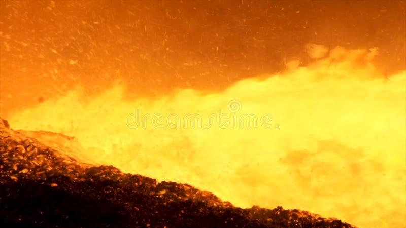 Ciérrese para arriba para el metal líquido que fluye del horno en la planta metalúrgica, concepto de la industria pesada Colada f imágenes de archivo libres de regalías