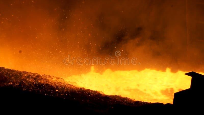 Ciérrese para arriba para el metal líquido que fluye del horno en la planta metalúrgica, concepto de la industria pesada Colada f fotos de archivo