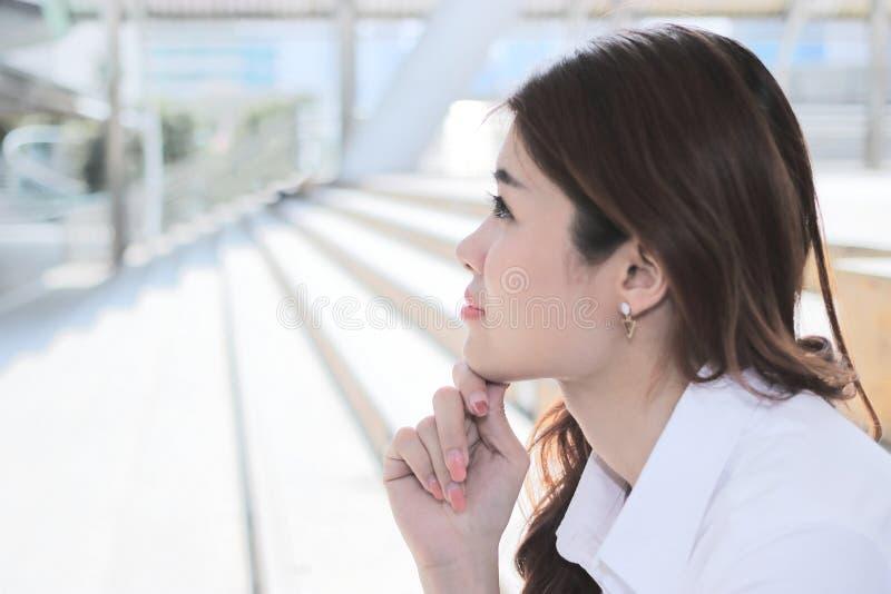 Ciérrese para arriba en cara de la mujer asiática joven hermosa que se sienta en la escalera y que mira lejos con el espacio de l fotografía de archivo