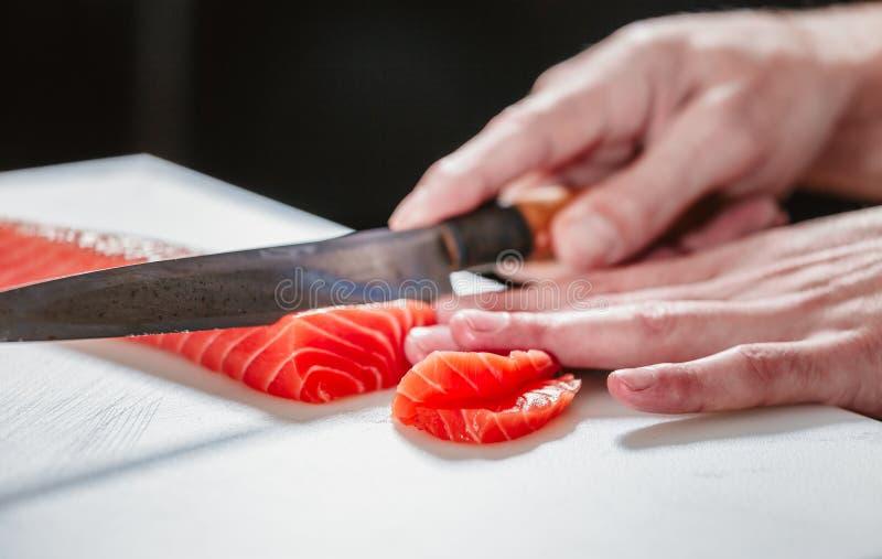 Ciérrese para arriba en cortar salmones crudos con el cuchillo afilado imagen de archivo libre de regalías