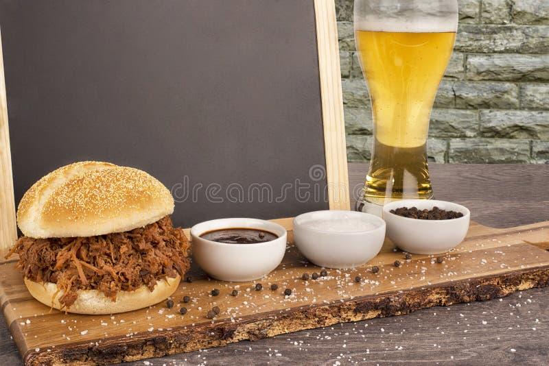Ciérrese para arriba en el bocadillo tirado del cerdo y la cerveza rubia en tablón de madera foto de archivo