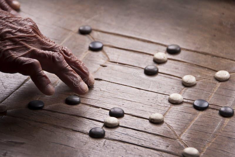 Ciérrese para arriba en la mano de un viejo hombre que juega al juego del molino imágenes de archivo libres de regalías