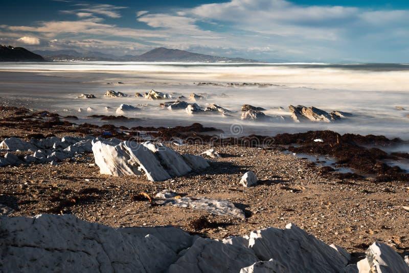 Ciérrese para arriba en la playa arenosa hermosa con las rocas en costa atlántica en bidart en la exposición larga por la mañana  fotos de archivo