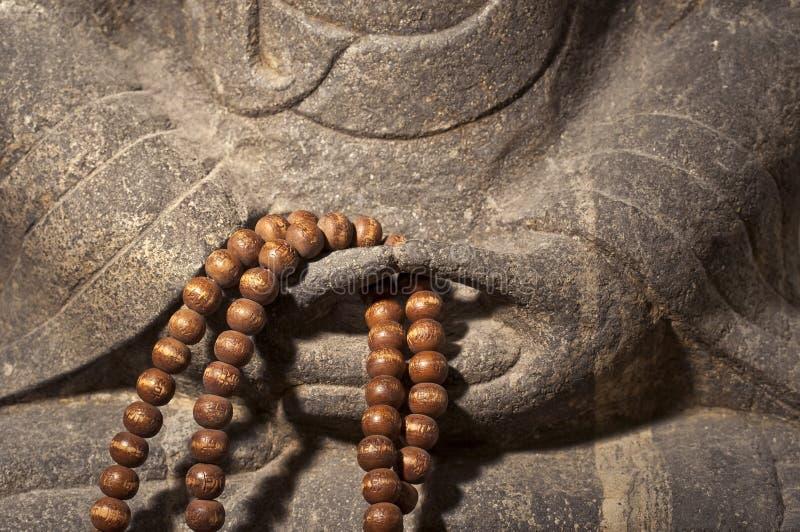 Ciérrese para arriba en las manos de una estatua de Buda que sostienen un rosario de madera de las gotas de rezo foto de archivo