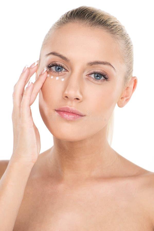 Ciérrese para arriba en las mujeres hermosas que aplican la crema cosmética de la crema hidratante en cara fotos de archivo libres de regalías