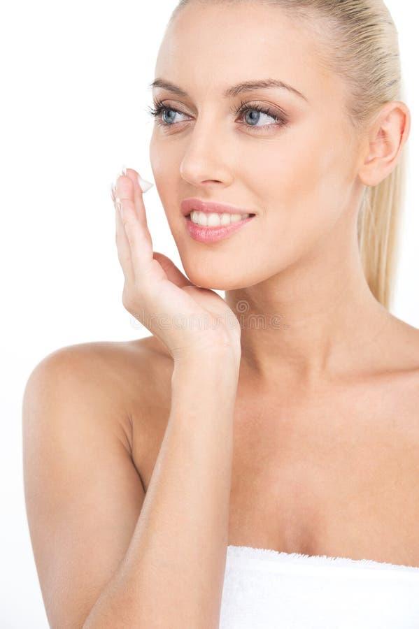 Ciérrese para arriba en las mujeres hermosas que aplican la crema cosmética de la crema hidratante en cara foto de archivo libre de regalías