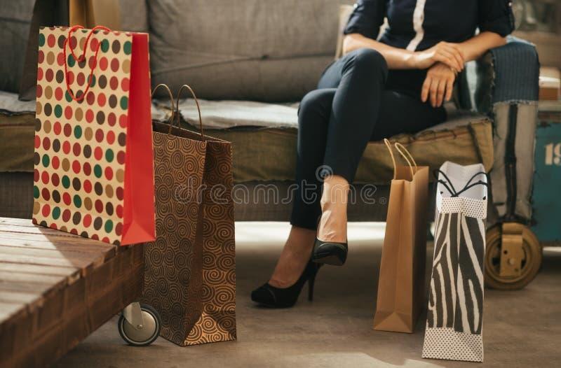 Ciérrese para arriba en los panieres y mujer en el sofá en fondo foto de archivo