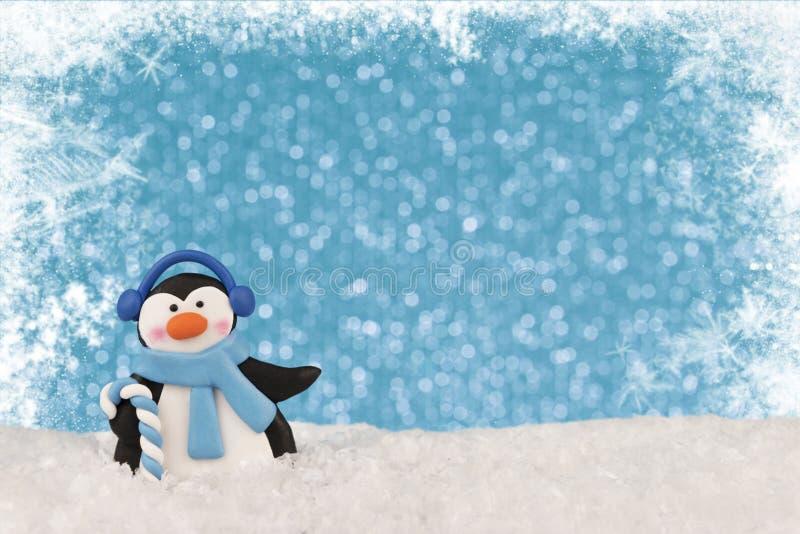 Ciérrese para arriba en un pingüino de baile, luces azules del bokeh en fondo y copos de nieve en frontera fotos de archivo