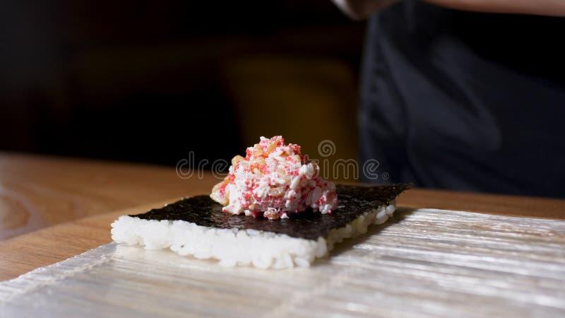 Ciérrese para arriba para las manos del cocinero en los guantes negros que ponen el relleno con el caviar rosado en la hoja y el  fotografía de archivo libre de regalías