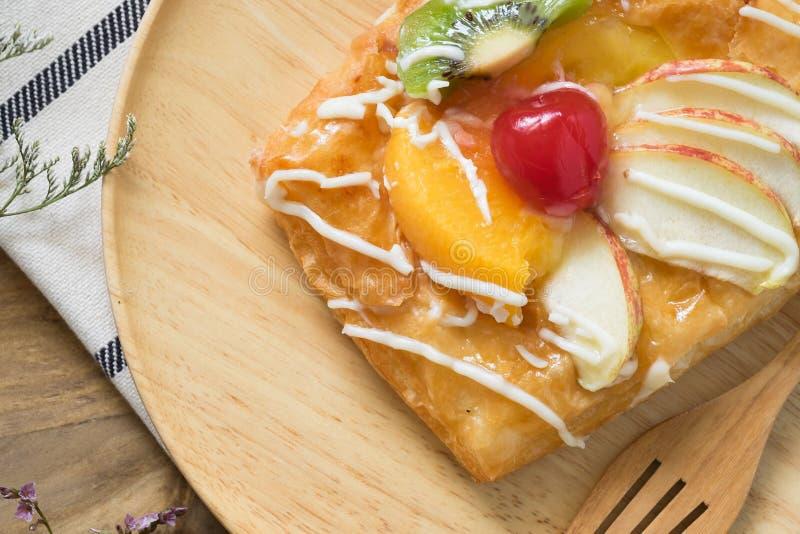 Ciérrese para arriba, los pasteles daneses de la visión superior con la fruta en el plato de madera imágenes de archivo libres de regalías