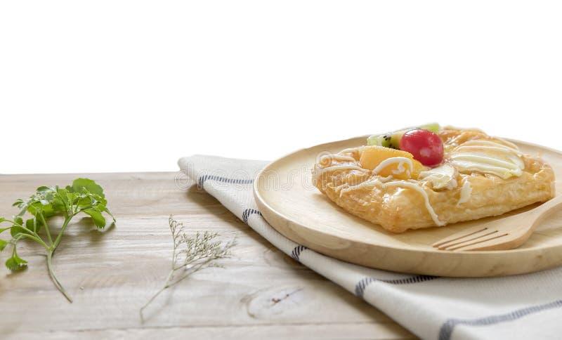 Ciérrese para arriba, los pasteles daneses de la visión superior con la fruta en el plato de madera foto de archivo