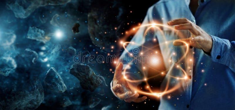 Ciência abstrata, mãos que guardam a partícula atômica, energia nuclear imagem de stock