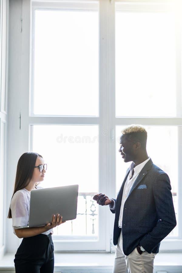 Ciò è esso Giovane donna asiatica graziosa di affari che indica al computer portatile mentre stando vicino al suo uomo felice di  fotografie stock libere da diritti