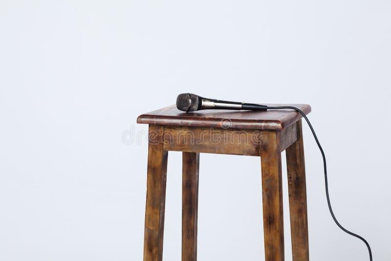 Ciò è una foto di un microfono che si siede sopra un panchetto di legno lite da sopra Sparato su una priorità bassa bianca fotografia stock