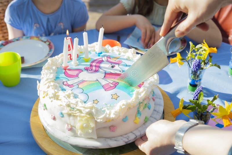 Ciąć urodzinowego tort z jednorożec charakterem fotografia stock