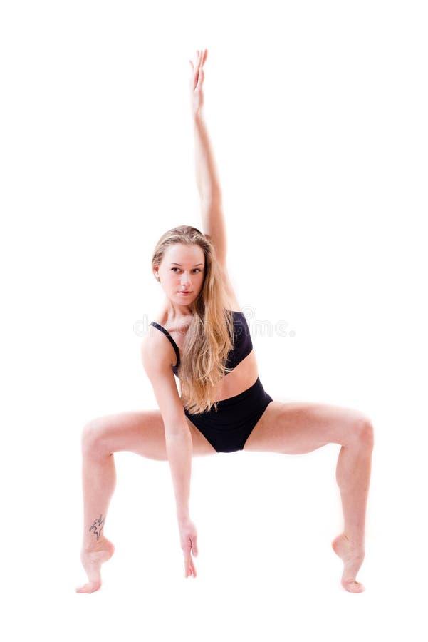 Ciągliwa elastyczna piękna blond młoda seksowna kobieta wykonawcy tancerza pozycja na tiptoe zginał kolana odizolowywających na b obrazy royalty free