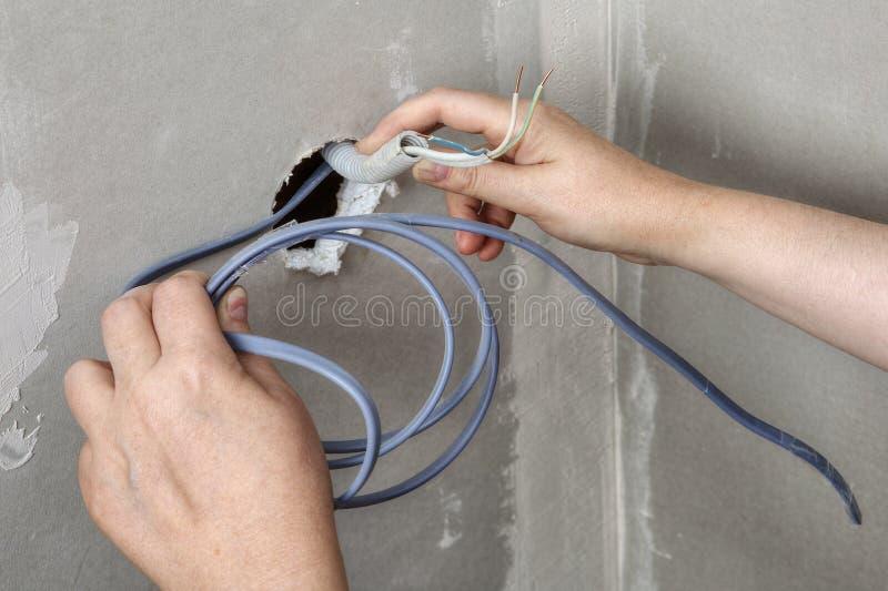 Ciągnący depeszuje przez ściennej dziury, elektryk ręk zakończenie obraz stock