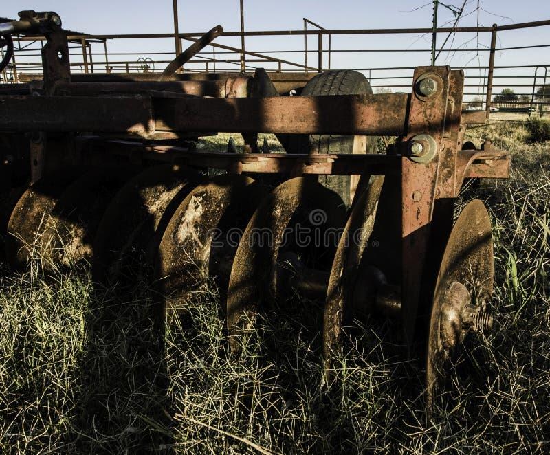 Ciągnik ciągnący pług z rdzewiejącymi ostrzami w zakończenie up szczególe fotografia royalty free