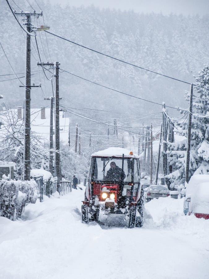 Ciągnik czyści drogę po ciężkiego opadu śniegu zdjęcie stock