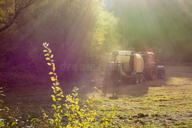 Ciągnik i baler zbiera siano lub trawy zdjęcia royalty free