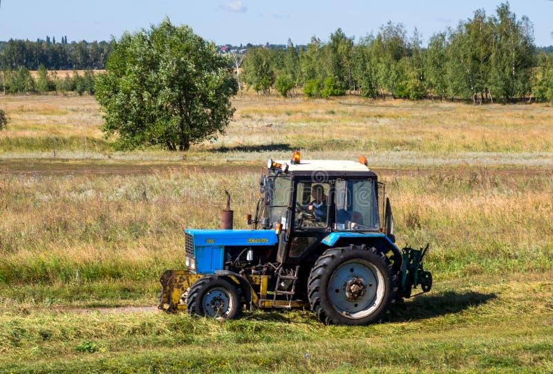 Ciągnik jedzie na krawędzi pola w wsi obraz stock