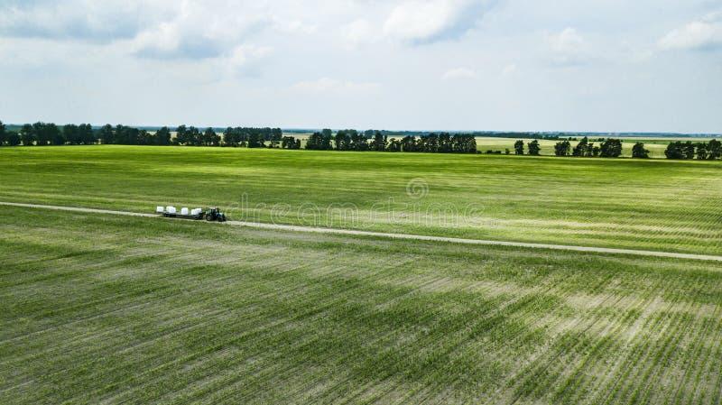 Ciągnik jedzie na polu i niesie bele siano widok z lotu ptaka obrazy stock