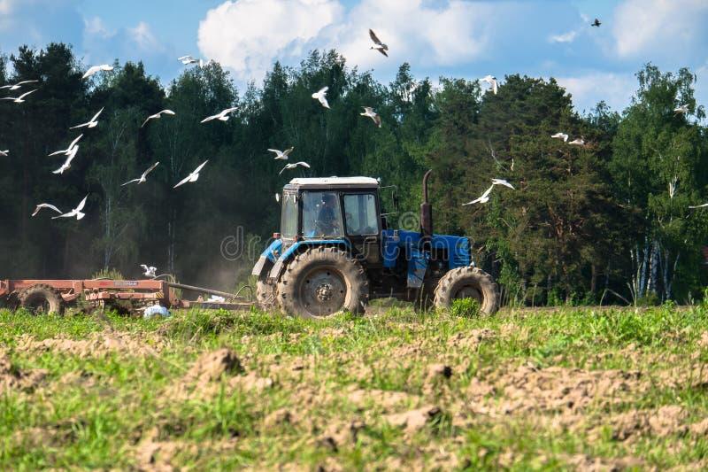 Ciągnik orze pole na jaskrawym słonecznym dniu Wiosna wiejski krajobraz obrazy stock