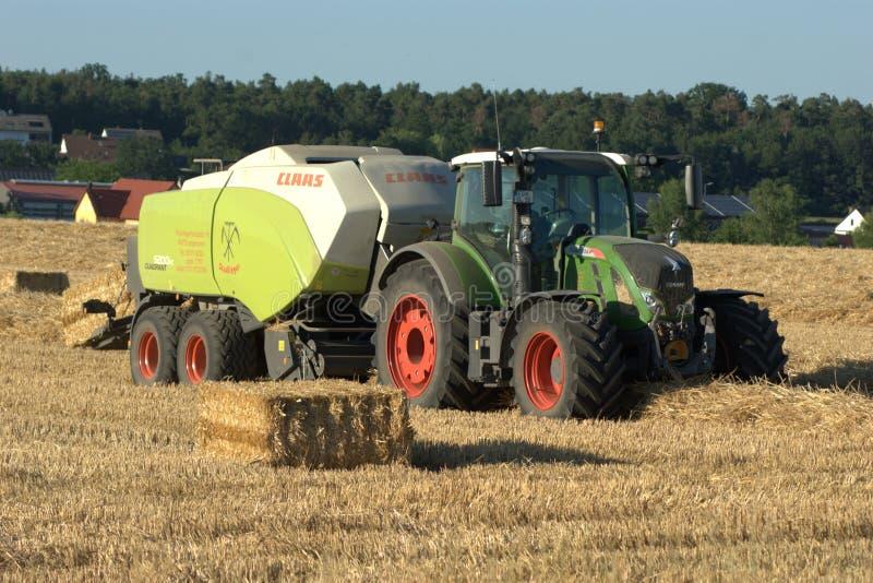 Ciągnik rolniczy ciągnący automatyczną siankę i słomę do belowania obraz royalty free