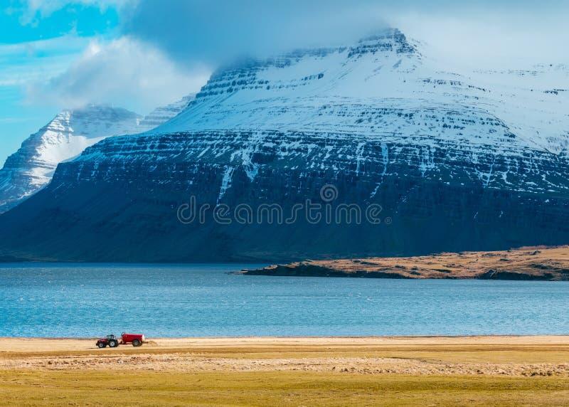 Ciągnik w polu z zadziwiać śnieżne góry w tle obraz stock