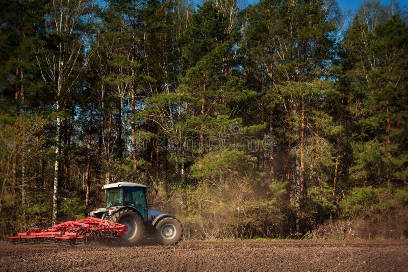Ciągnik z maszyną na krawędzi przeorzący pole przy lasem obraz stock