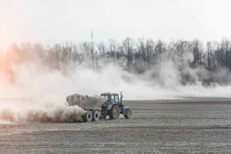 Ciągnik z przyczepą nawozi rolniczego pole w wiośnie dla wysiewnej kukurudzy zdjęcie stock