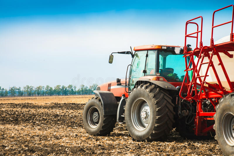 Ciągnik z zbiornikami w polu Rolnicza maszyneria i uprawiać ziemię obrazy royalty free