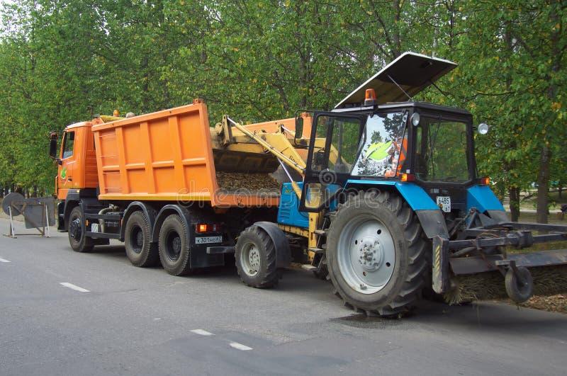 Ciągnikowi ładunki spadać liście od pobocza w ciężarówce fotografia stock