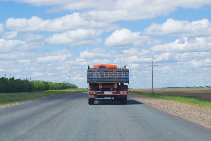 Ciężarówka biega na autostradzie pod niebieskim niebem fotografia stock
