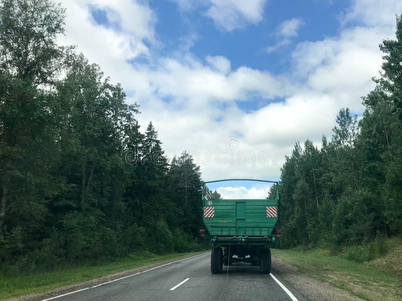 Ciężarówka, ciągnik z wielką zieloną przyczepą jedzie wzdłuż lasowej asfaltowej drogi z zielonymi drzewami na ziemiach fotografia stock
